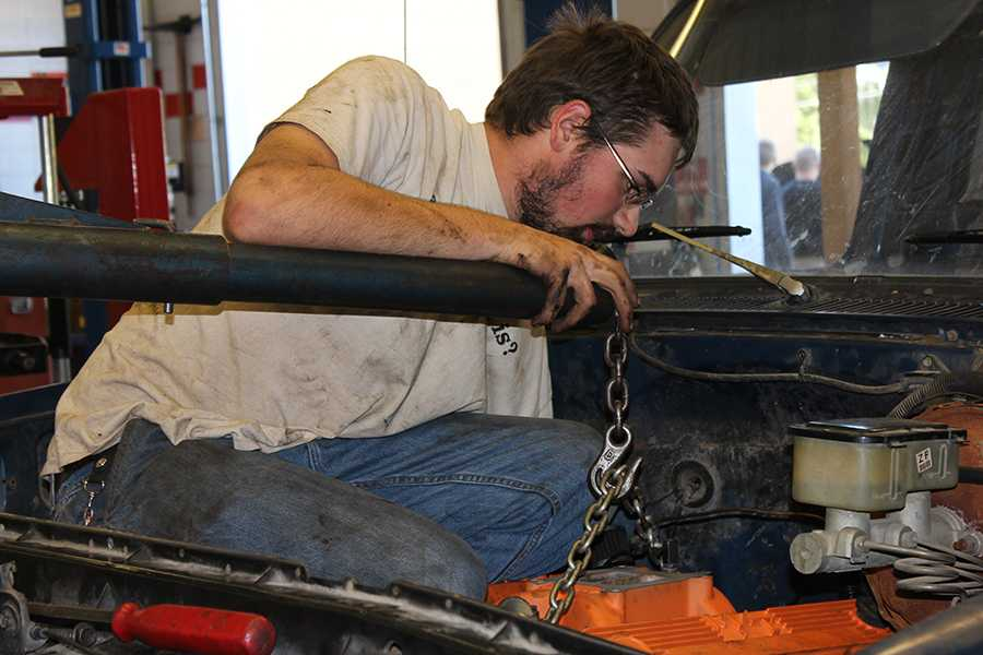 Working in the autos shop, Kin Staton (12) lowers the rebuilt engine into his truck on Sep. 29.