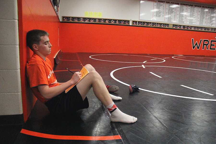 Before wrestling practice, Daniel Woods (10) rewrites the five goals he chose at the beginning of the season.