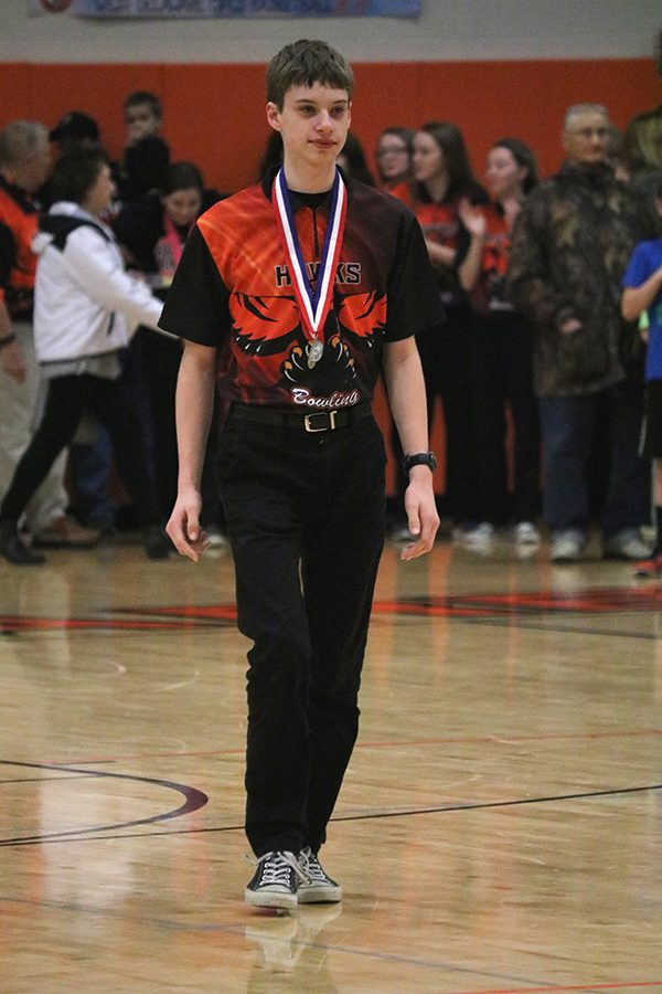 After receiving second place at the Class 1A State Bowling Tournament, sophomore Alex Schnieders walks in front of the crowd after the boys' basketball game. Schnieders bowled a two-game series of 472, placing behind junior Jeff Boeckenstedt, the Individual State Champion. (481).