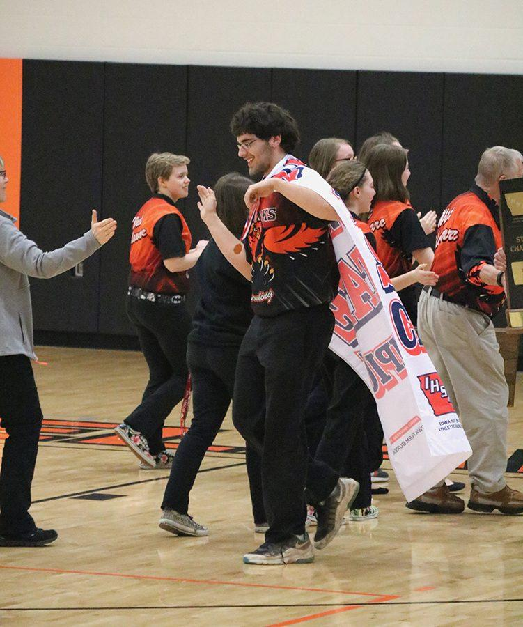 With the State Champion Banner displayed on his back, senior Blaine Wilson gives Coach Sue Morris a high five. Wilson bowled a two-game series of 370.