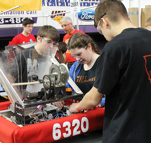 Colby Samuelson (9), Taylor Cherry (11) and Tyler Salow (10) examine the robot before competition.