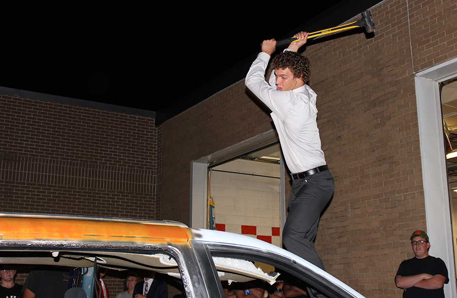 Harrison Goebel, senior, takes a swing at the car bash following coronation Monday night. Students paid $1 for three swings at the van.
