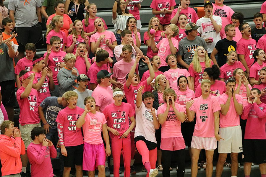 Supporting+the+volleyball+girls%2C+the+crowd+cheers+them+on+while+wearing+pink.