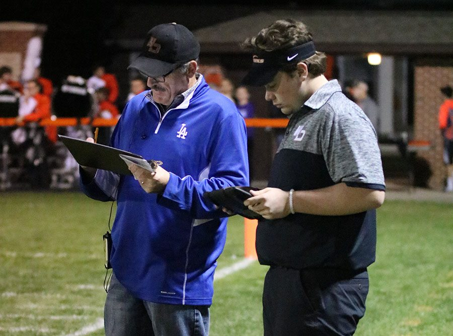 Bill Logan and Dylan Linderwell (12) record stats at the home football game on Oct. 20.