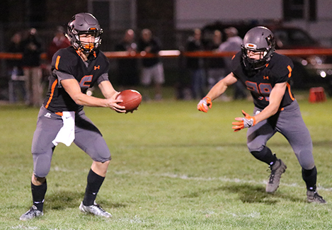 Quarterback Mitchel Mangold (11) hands the ball off to running back Kale Rempe (10) during the Maquoketa game.