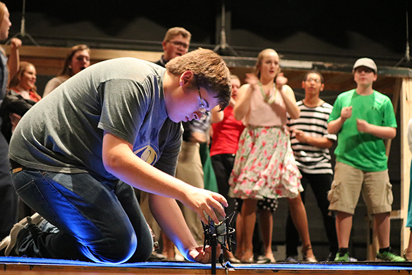 Colby Samuelson (10) adjusts a microphone on stage. This year, students had the opportunity to work with UNI's AKG microphones.