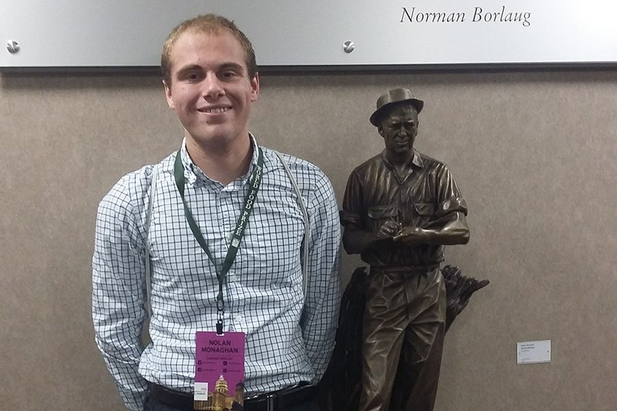 Nolan Monaghan (12) stands alongside the Norman Borlaug statue.