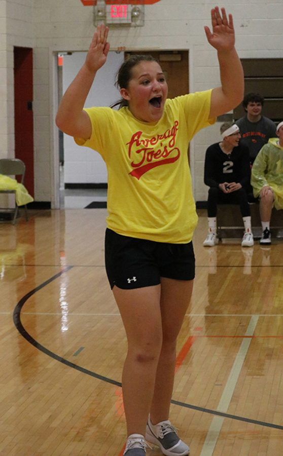 Celebrating a point, junior Claire Rausch extends her hands up to high five a teammate.