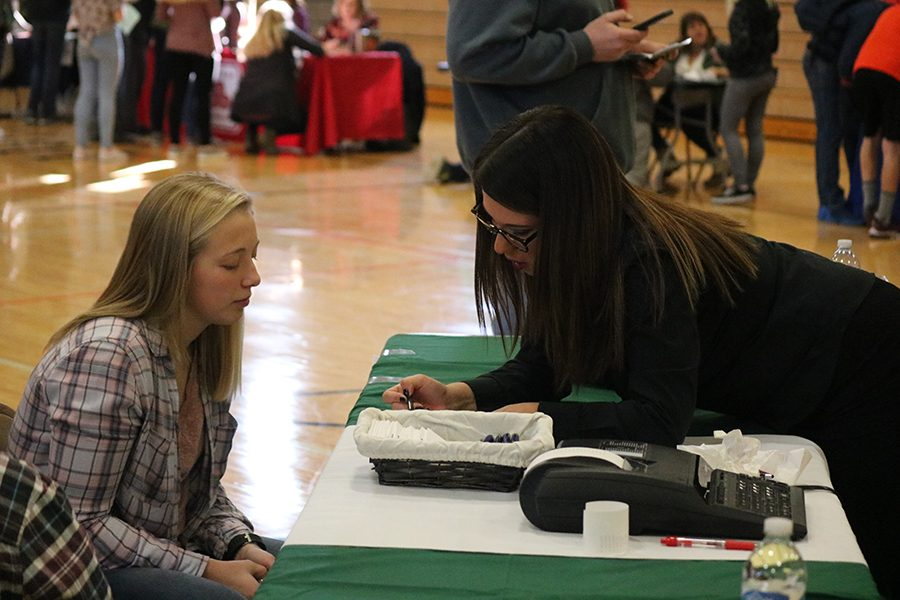 Paying a visit to the bank, Bailey Beckman (12) consults with a volunteer. Students visited the bank to double check the amount they spent.