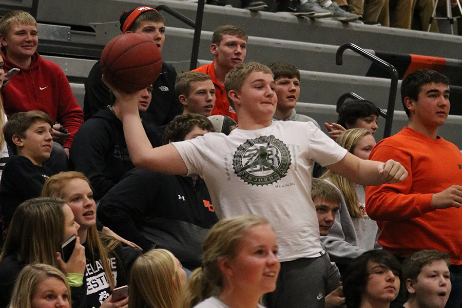 Trying to make the basketball in the hoop, freshman Gavin Tucker launches the ball from the student section.