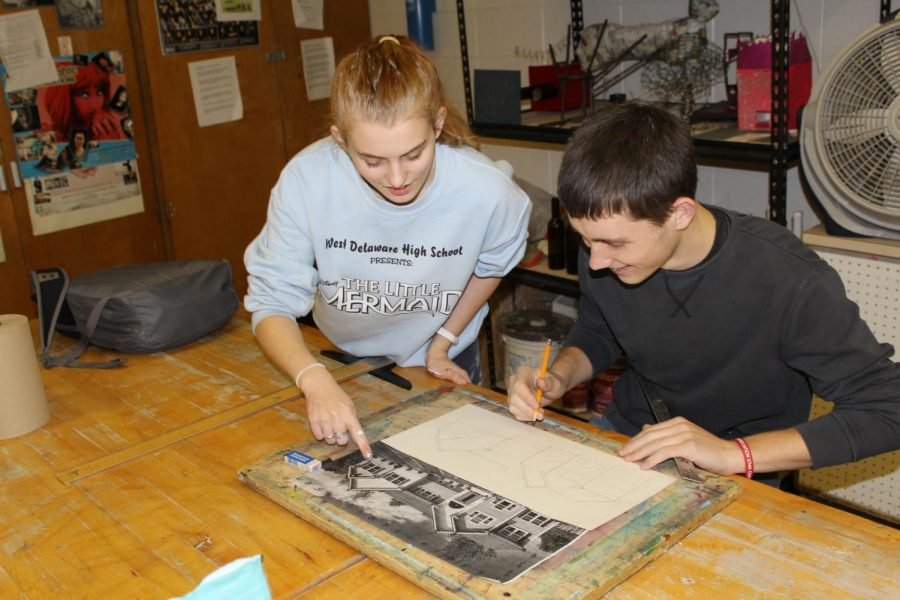 While working in art class, senior Paris Schaul gives junior Devon Gardner advice on his drawing.