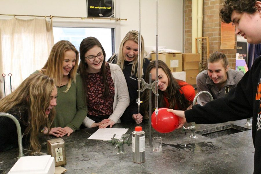Juniors Maggie McGrane, Maddy Gray, Megan McDonald, Hayley Cook, Ally Martin, and Emily Klostermann laugh while cadet Nic Wulfekuhle (12) performs an experiment. The class learned about different types of bonds during the experiment.