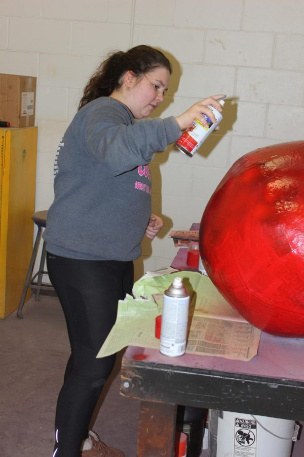 Karley Vantheemsche (11) spray paints a Christmas ornament to be displayed in the cafeteria.