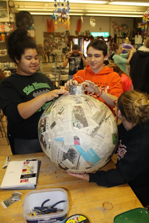 Adaja Collins (11), and Devon Gardner (11) use the power of teamwork to put together one of the Christmas balls in art class.