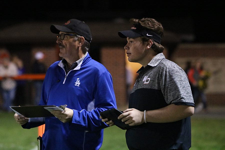 BIll Logan, sideline reporter, and Dylan Linderwell (12) watch closely as the athletes make their play.