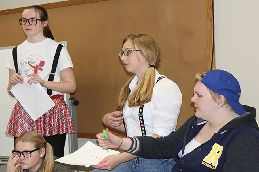 Freshmen Morgan Collier, Brooke Holtz and Mikaila Neuzil portray geeks that are frightened by Brynn Boeckenstedt's jock persona during their choral reading practice.