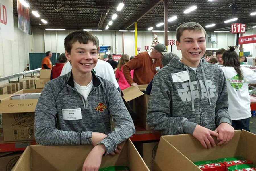 Grinning from ear to ear, Freshmen Matt Mensen and Nick Stocks help sort and scan gifts for Operation Christmas Child.