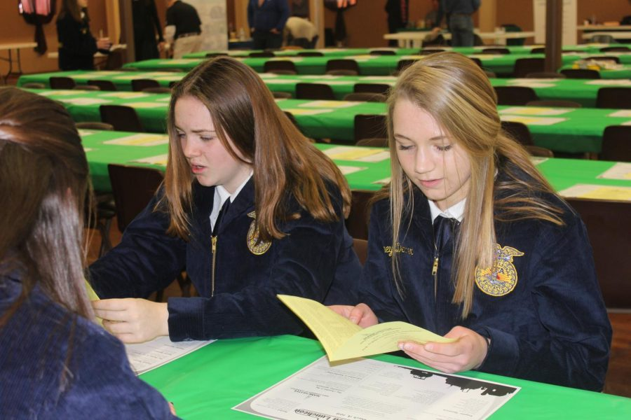 Mia Peyton (9) and Laney Demmer (9) look over the agenda for the day.