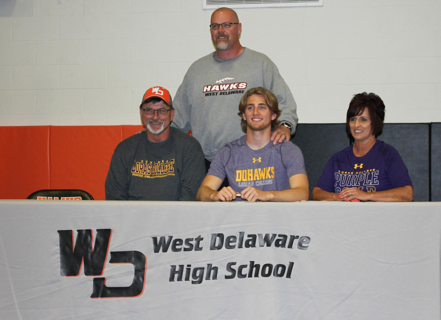 After signing with Loras Cook poses with his parents and coach Doug Winkowitsch.