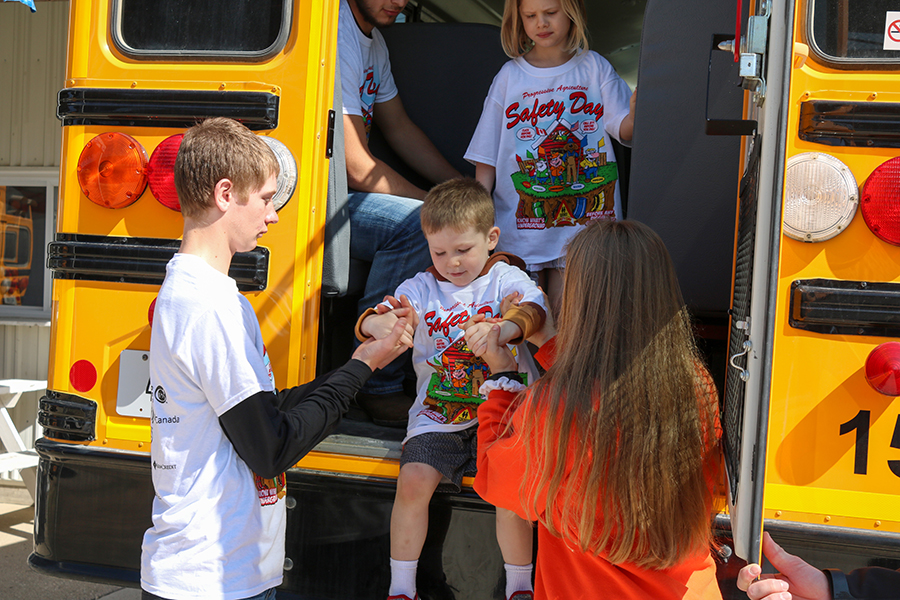 Zach Goebel (10) and Alexis Hartman (9) safely help students off the bus after learning about bus safety.