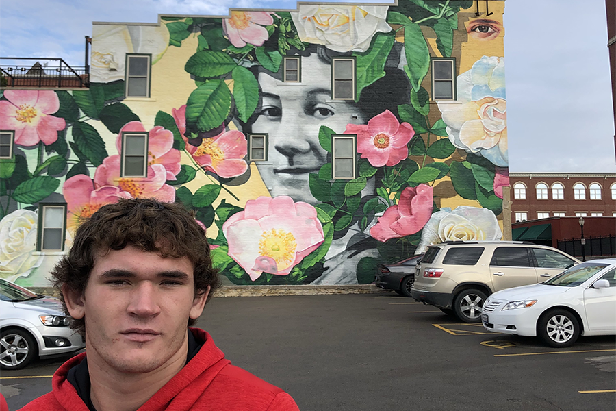Junior Jack Neuhaus poses in front of a mural on their art trip.