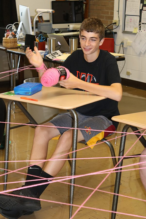 As sophomore Carson Schnieders wraps the yarn around his hand, he answers a question about his family.