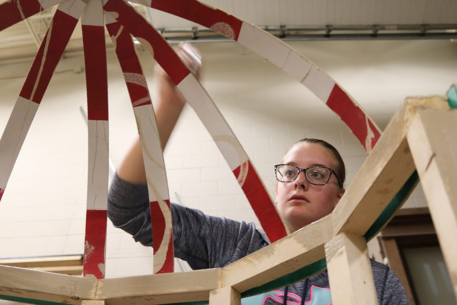 Grace Reth (10) paints a bird cage for the villain, Ms. Andrews. All the painting of props and set are done by the students.