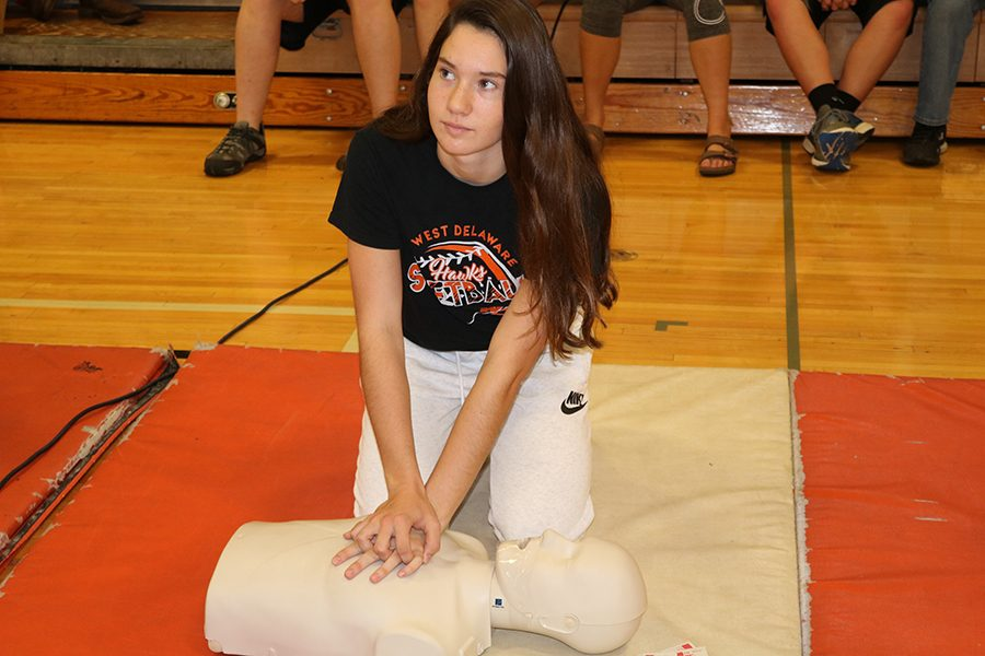 During first hour, freshman Jaci Bries learns how to provide CPR on a practice dummy in the gym. Teacher Jeff Voss taught CPR lessons to the freshman class so they could learn important skills now that Health I class is no longer required for graduation.