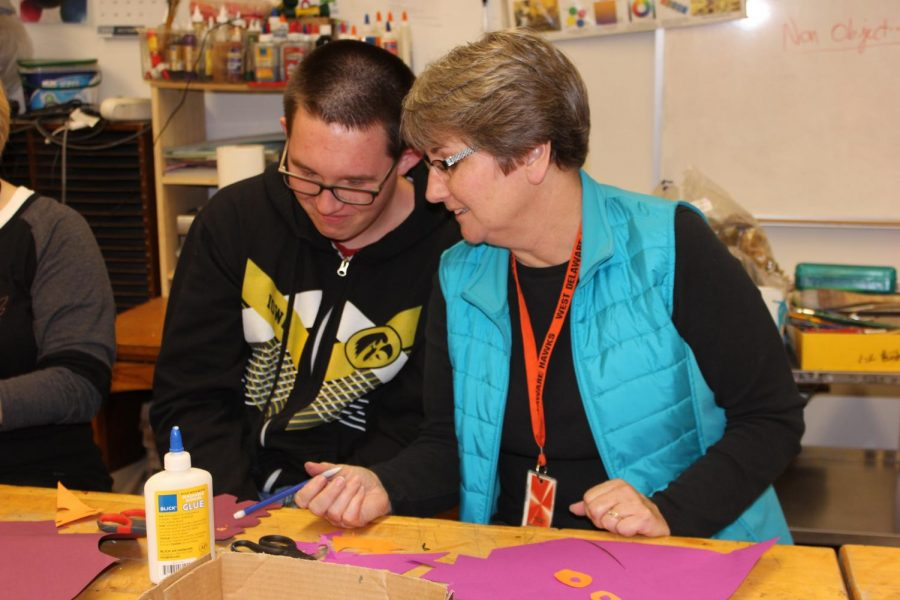 Darla Gaskill helps out sophomore Michael Mastin in art class.