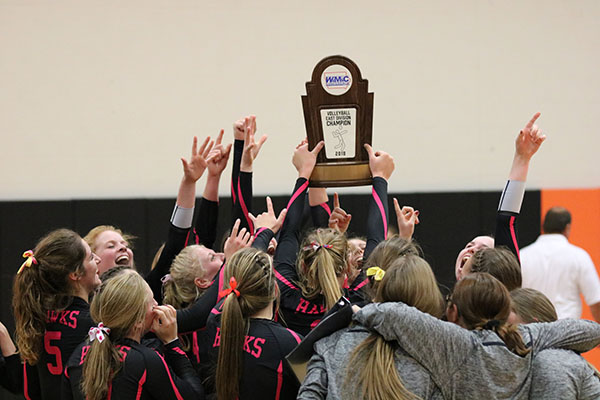 With+the+WaMaC+trophy+in+hand%2C+the+volleyball+team+celebrates+after+their++win.+The+Hawks+beat+Beckman+3-2.
