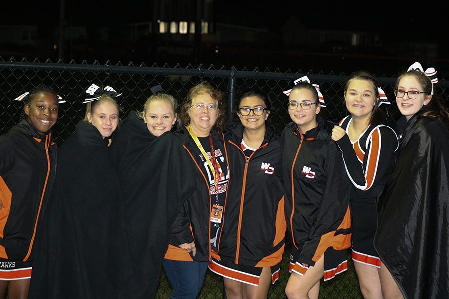 During half-time of the last football game, the cheerleaders huddle together to stay warm. From left: Reginetta Tate, Sydney Bliss, Peyton Carlson, Coach Angie Zehr, Destiny Callaway, Illiana Rohlf-McGraw, Chloe Wilson, and Austyn Isaacs.