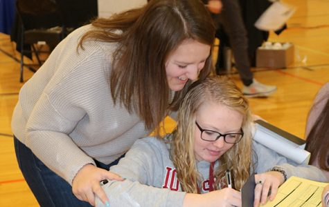 While at the charity and contributions table, seniors Claire Rausch and Lauren Ryan fill out a check.