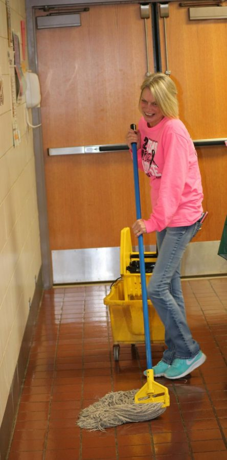 Tutton laughs as she mops the lunch line area before winter break.