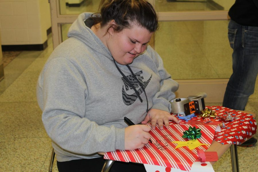 Senior Kaycee Elledge prepares a decoration to be placed on her homeroom door.