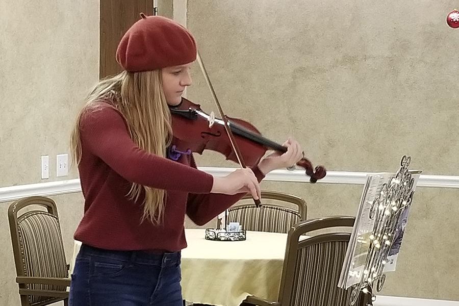 At the Window Walk, freshman Gracie McCusker plays her violin.