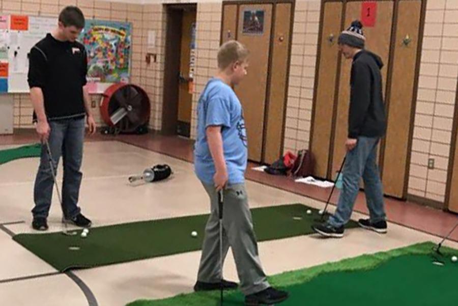 Tyler Langel (12), Brandon Larson (11), and Trevor Soppe (9) practice their putting skills on the indoor putting greens.