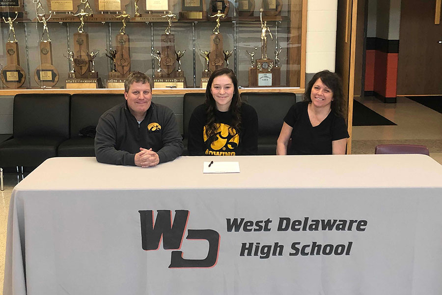 Lilly Meyer (12), with her parents by her side, signs for the University of Iowa Rowing team.