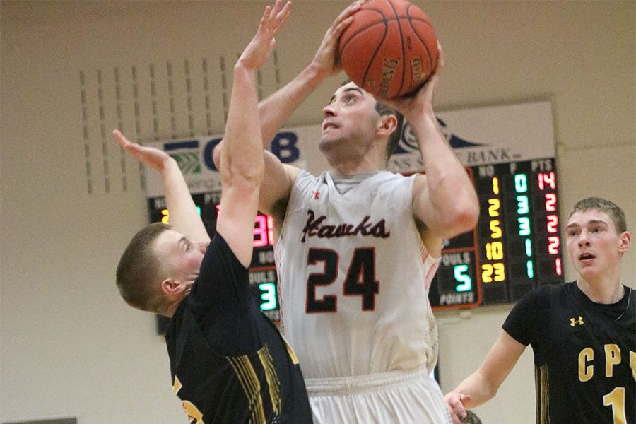 Senior Derek Krogmann goes up for a lay-up against Center Point Urbana in the second-round district basketball game. The Hawks won, 45-44.