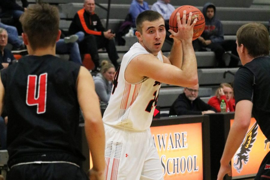 Avoiding defenders, Derek Krogmann (12) looks for an open teammate. Krogmann scored 512 points on the season and broke the school's all-time point and rebound records with a career total of 1,679 points and 1128 rebounds.