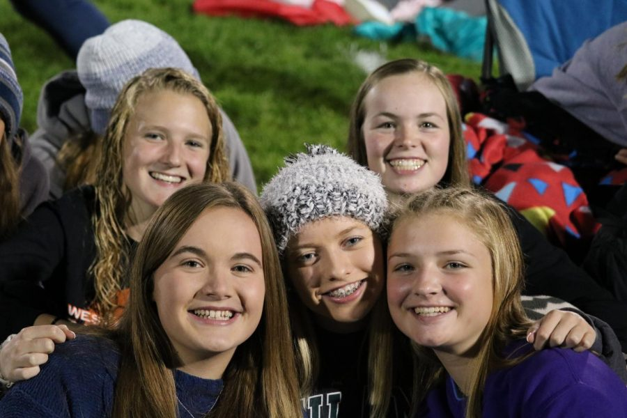 Faith Litterer (9), Anna Werner (11), Jadyn Werner (11), Morgan Collier (11) and Makayla Gasper (10) huddle together to keep warm while listening to the guest speaker at Fields of Faith.