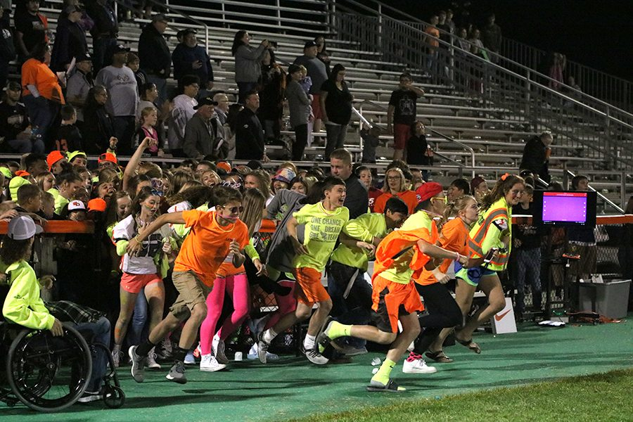 Students+charge+the+field+decked+out+in+neon+on+Sept.+6.+The+Hawks+beat+the+Marion+Indians+with+a+win+of+32-20+that+night.