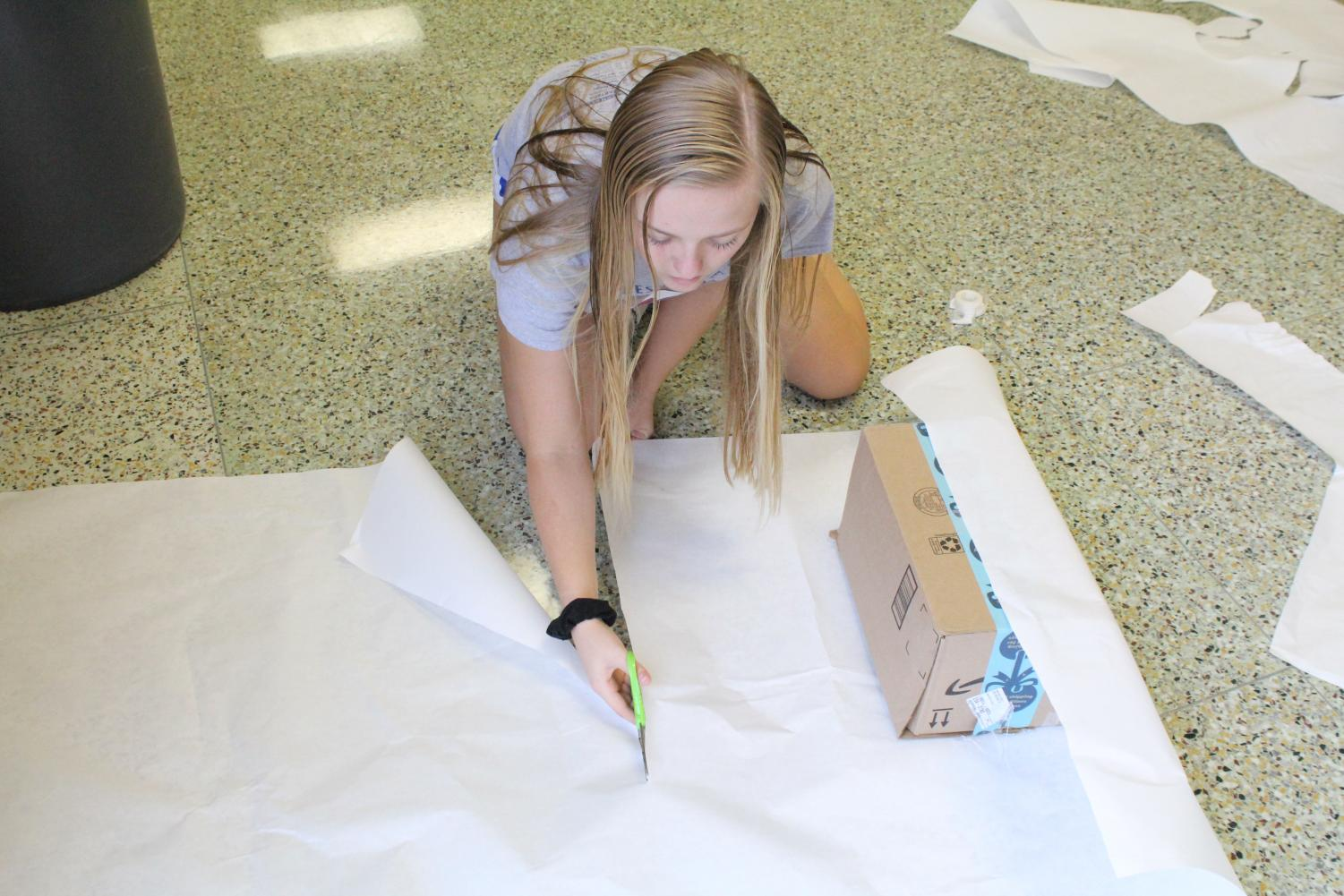 Wrapping a present for the Winter- themed hallway, sophomore Kylinne Meyers cuts off a piece of white paper at homecoming decorating.