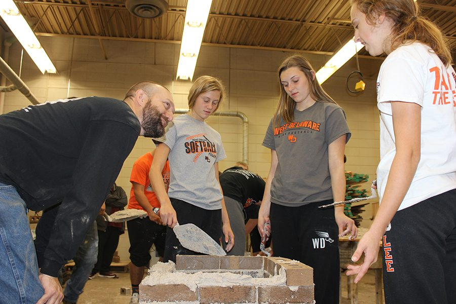 During masonry day, teacher Seth Harms teaches freshmen Alivia Shulte, Keara Emerson, and Riley Lee how to build walls and chimneys out of brick.