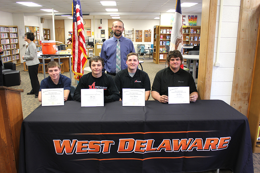 Seth Harms smiles proudly with the four certificate recipients, Bo Juran, Jeff Ilgen, Dakota Waterhouse and Jacob Brown, at the graduation ceremony on Nov. 4.