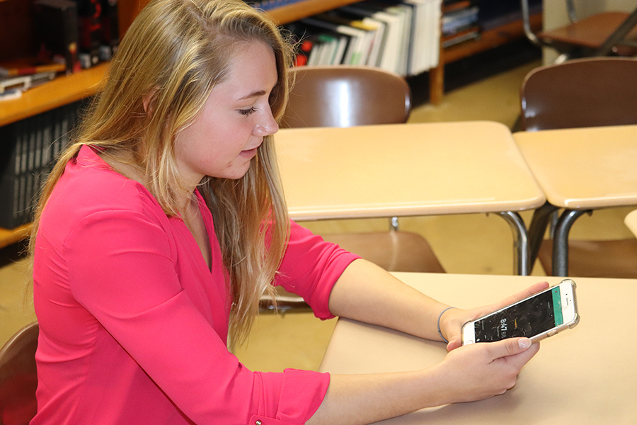 Accessing her Pocket Points app, Laney Demmer (11) begins to receive points. Demmer uses the app everyday in English III class and has earned extra credit and the option to leave early for lunch.