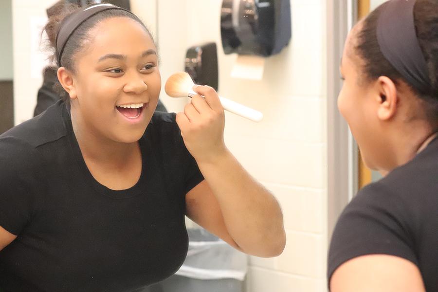 On an all-day Saturday practice, Kamira Zehr (9) applies makeup.