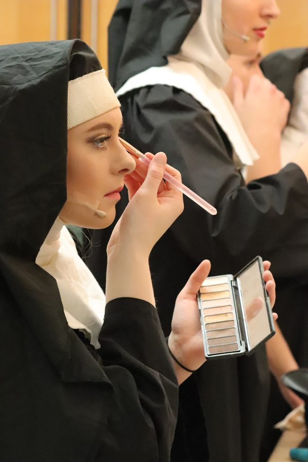 Concentrating on fixing her makeup, Karsyn Welcher (11) prepares for a practice on Saturday Nov. 2. Welcher played multiple roles in the musical, including backup singer/dancer, a nun, and a fantasy dancer.