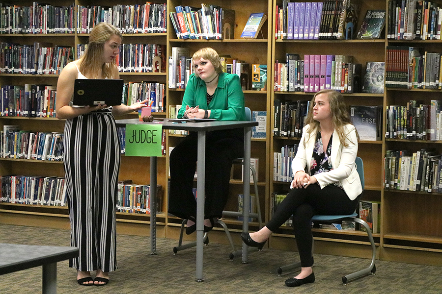 Taylor Hammer (11) questions Molly Mullis (11) on her involvement as Reverend Hale in the Advanced English III Mock Trial while Brynn Boeckenstedt (11) keeps order as the judge.