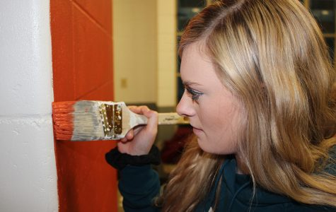 Karsyn Welcher (11) paints the final touches on the new accent wall in the old girls locker room.
