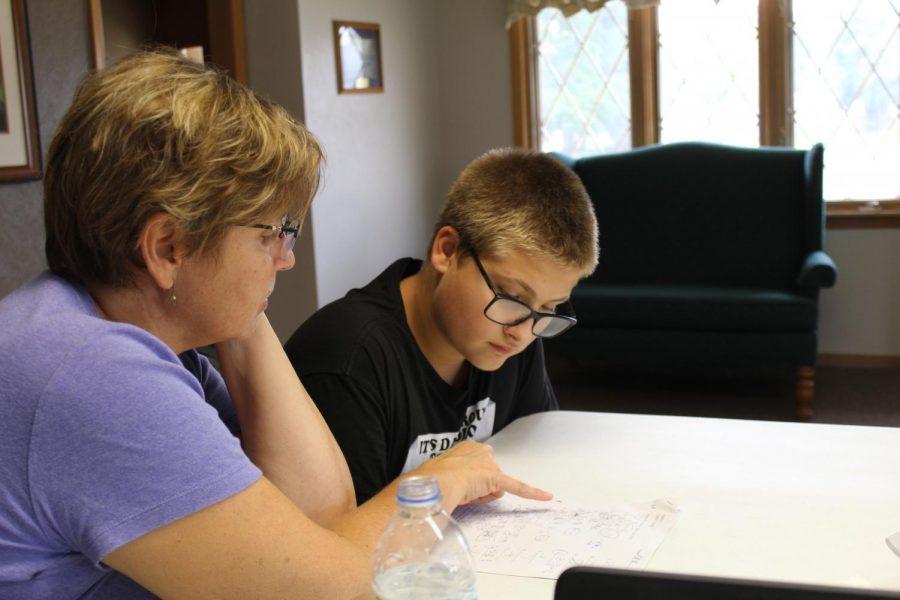 Darla Weber helps Adrian Swenka (9) understand a math problem.
